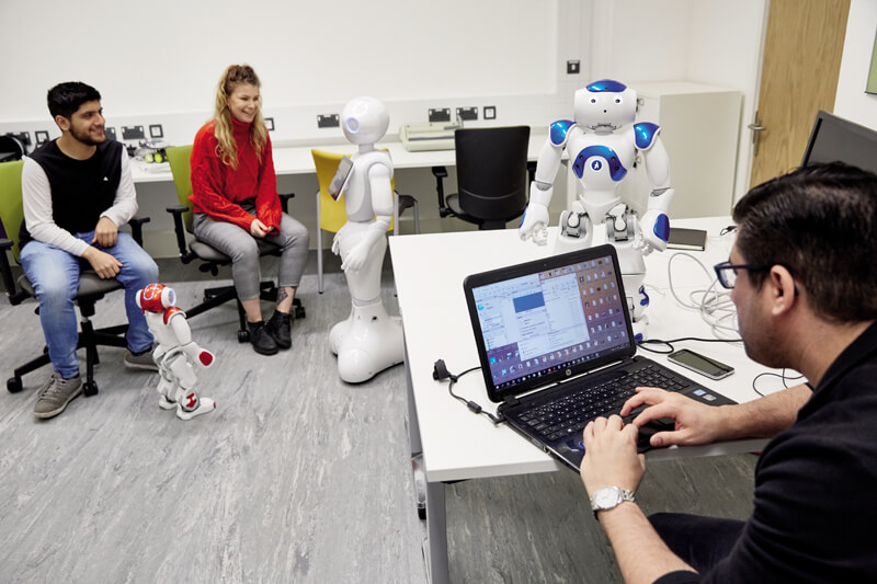 Computer science students using a Robot in a classroom